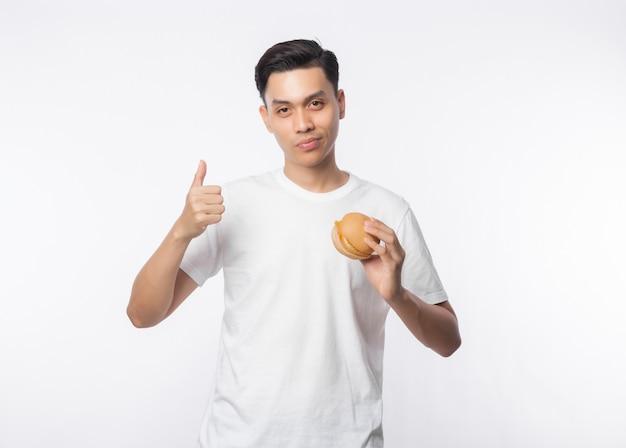 Junger asiatischer mann im weißen t-shirt, das hamburger hält und daumen oben lokalisiert auf weißer wand zeigt Premium Fotos