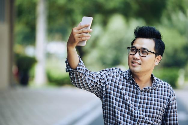Junger asiatischer mann in den gläsern und im karierten hemd, die selfie mit smartphone nehmen Kostenlose Fotos