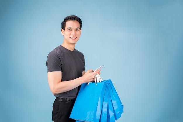 Junger asiatischer mann mit einkaufstaschen benutzt einen handy und lächelt beim handeln des einkaufens Premium Fotos