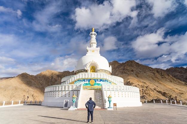 Junger asiatischer mannreisender, der die ansicht von shanti stupa auf einem gipfel in leh, ladakh, indien genießt Premium Fotos