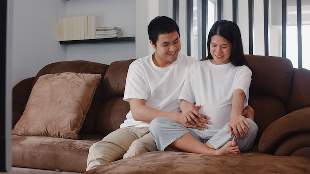 Junger asiatischer schwangerer paarmann berühren seinen fraubauch, der mit seinem kind spricht. die mutter und vati, die glücklich lächeln friedlich sich fühlen, während mach s gut baby, die schwangerschaft, die zu hause auf sofa im wohnzimmer liegt. Kostenlose Fotos