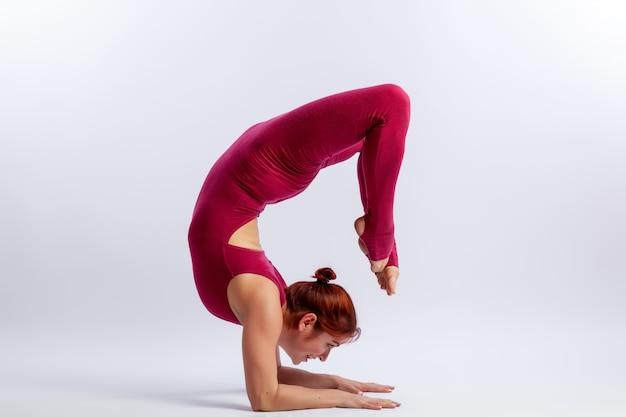 Junger athletischer frauenturner im gymnastischen overall tut das ausdehnen in schwierige haltungen Premium Fotos