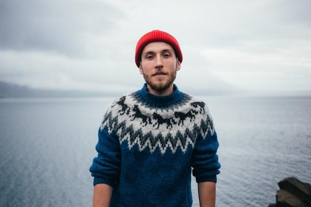 Junger attraktiver bärtiger tausendjähriger mann im roten fischer- oder matrosenmützenhut und im traditionellen blauen pullover der isländischen verzierung Kostenlose Fotos