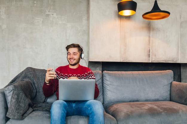 Junger attraktiver mann auf sofa zu hause im winter mit smartphone in kopfhörern, musik hörend, roten strickpullover tragend, am laptop arbeitend, freiberuflich, lächelnd, glücklich, positiv, tippend Kostenlose Fotos