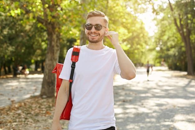 Junger attraktiver mann in der sonnenbrille, die im park geht, lässige kleidung und roten rucksack tragend, in den hörer, positives emotionskonzept setzend Kostenlose Fotos