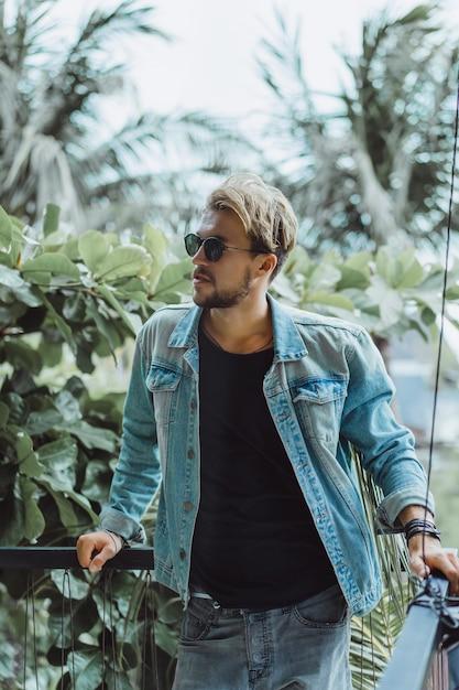 Junger attraktiver mann posiert in einem tropischen ort, auf einem hintergrund von palmen und grün Kostenlose Fotos