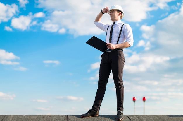 Junger attraktiver vorarbeiter im weißen sturzhelm, in der bindung und in den klammern stehen auf dem dach mit tablette Premium Fotos
