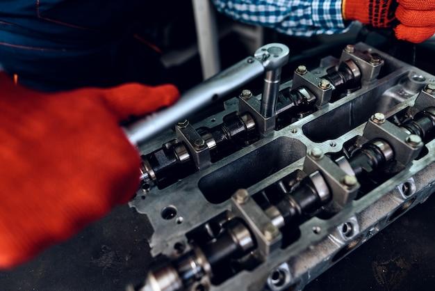 Junger automechaniker verdreht eine nuss. tankstellenkonzept. Premium Fotos