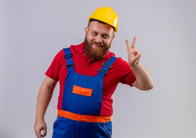 Junger bärtiger baumeistermann in der bauuniform und im sicherheitshelm, der kamera lächelnd zeigt und mit den fingern nummer zwei oder siegeszeichen oben zeigt Kostenlose Fotos