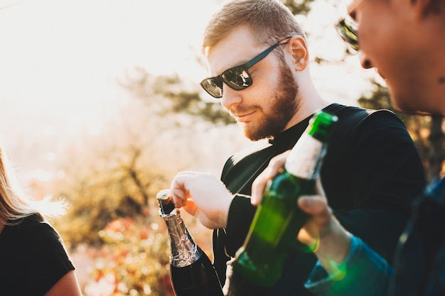 Junger bärtiger kerl in der sonnenbrille, die flasche champagner öffnet, während mit freunden in der landschaft feiert Premium Fotos