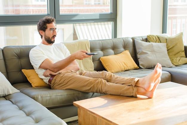 Junger bärtiger kühler mann, der auf einer couch zu hause sitzt Premium Fotos