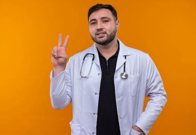 Junger bärtiger männlicher arzt, der weißen kittel mit lächelndem stethoskop trägt, das nummer zwei oder siegeszeichen zeigt Kostenlose Fotos
