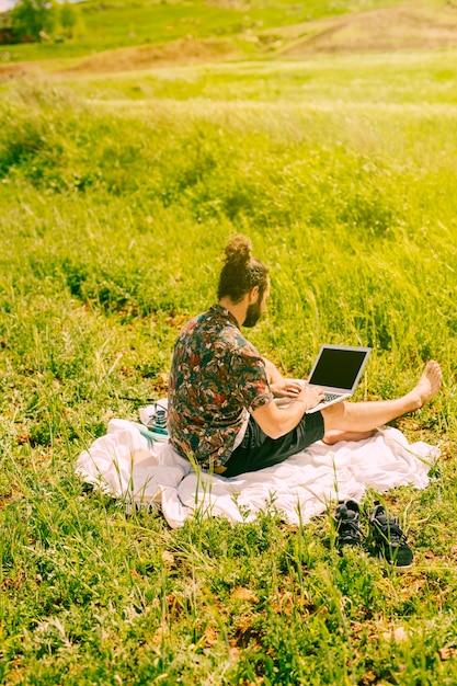 Junger bärtiger mann, der mit laptop auf dem gebiet sitzt Kostenlose Fotos