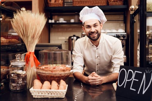 Junger bärtiger mann im schutzblech, das in der bäckerei steht. Premium Fotos