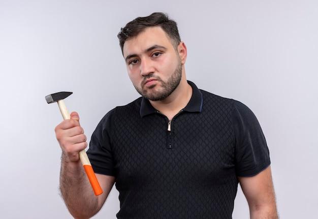 Junger bärtiger mann im schwarzen hemd, das hammer hält kamera mit ernstem gesicht betrachtet Kostenlose Fotos