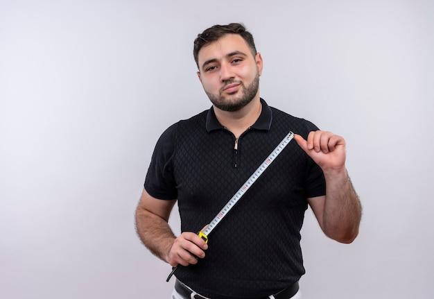 Junger bärtiger mann im schwarzen hemd, das maßband hält, das kamera betrachtet, die zuversichtlich lächelt Kostenlose Fotos