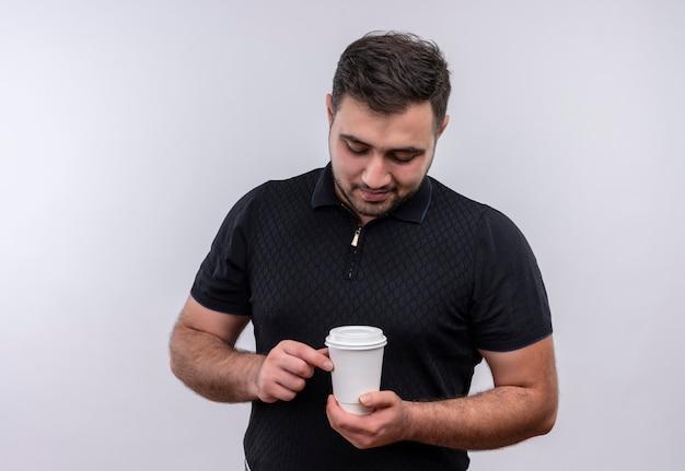 Junger bärtiger mann im schwarzen hemd, der kaffeekappe hält, die es mit lächeln auf gesicht betrachtet Kostenlose Fotos