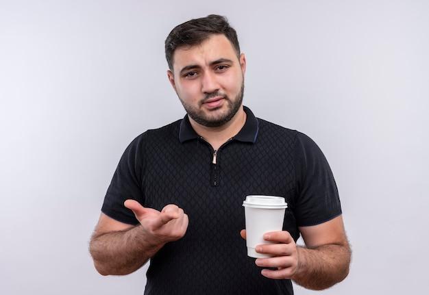 Junger bärtiger mann im schwarzen hemd, der kaffeetasse hält, die kamera missfiel, gestikuliert mit hand Kostenlose Fotos
