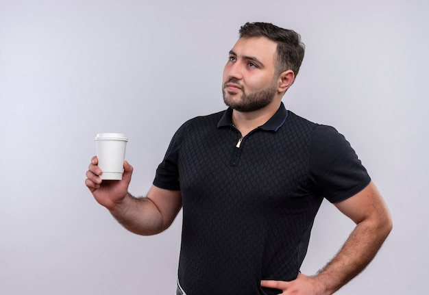 Junger bärtiger mann im schwarzen hemd, der kaffeetasse hält, die mit nachdenklichem ausdruck auf gesicht beiseite schaut Kostenlose Fotos