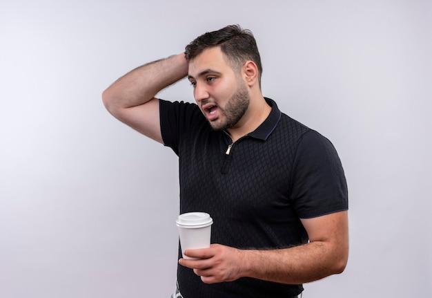 Junger bärtiger mann im schwarzen hemd, der kaffeetasse hält, die mit nachdenklichem ausdruck auf gesicht verwirrt betrachtet Kostenlose Fotos