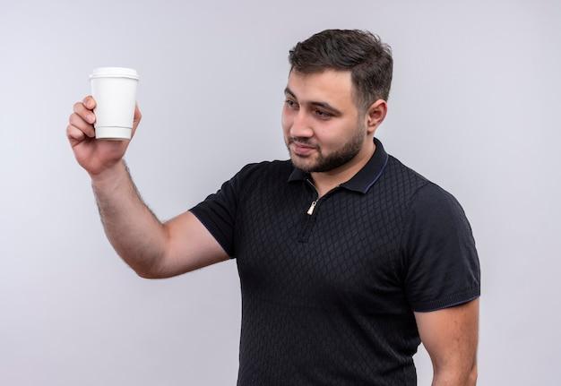 Junger bärtiger mann im schwarzen hemd, der kaffeetasse hält hand, die zuversichtlich lächelt Kostenlose Fotos