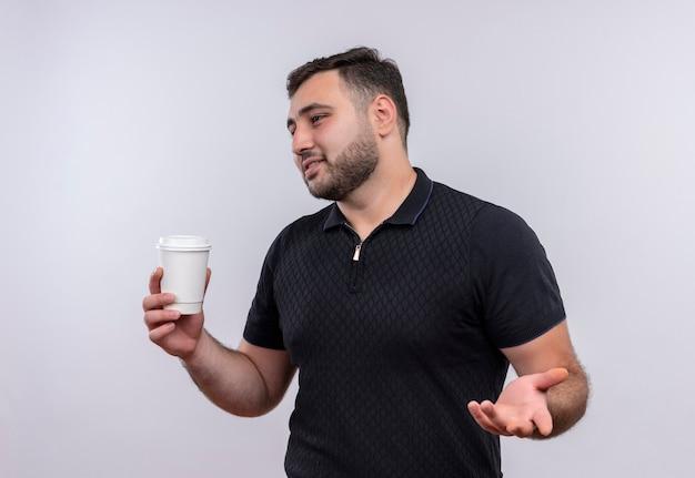 Junger bärtiger mann im schwarzen hemd, der kaffeetasse hält und beiseite schaut mit hand Kostenlose Fotos