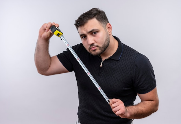 Junger bärtiger mann im schwarzen hemd, der maßband hält kamera mit ernstem gesicht betrachtet Kostenlose Fotos