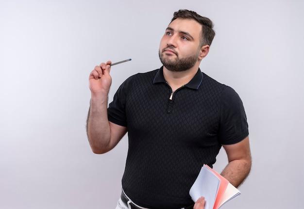 Junger bärtiger mann im schwarzen hemd, der notizbuch und stift hält, die mit pencive ausdruck beiseite schauen Kostenlose Fotos