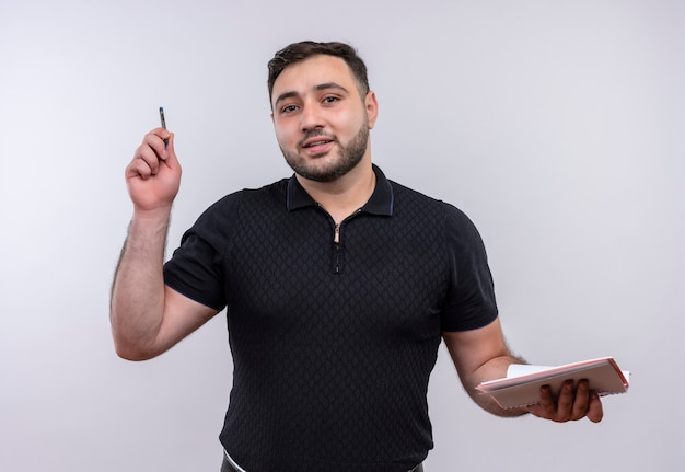 Junger bärtiger mann im schwarzen hemd, der notizbuch und stift hält, die zuversichtlich schauen Kostenlose Fotos