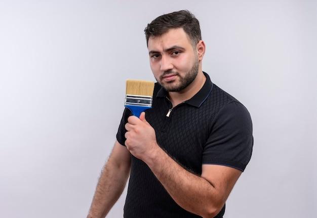 Junger bärtiger mann im schwarzen hemd, der pinsel hält kamera mit ernstem selbstbewusstem ausdruck betrachtet Kostenlose Fotos