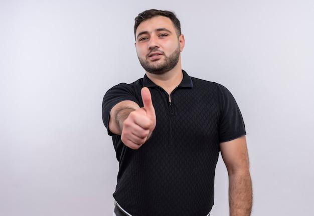 Junger bärtiger mann im schwarzen hemd glücklich und positiv, daumen hoch zeigend Kostenlose Fotos