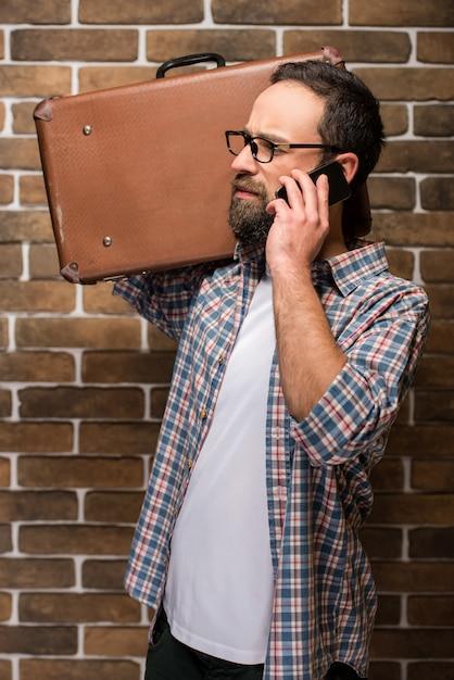 Junger bärtiger mann mit einem koffer auf seiner schulter. Premium Fotos