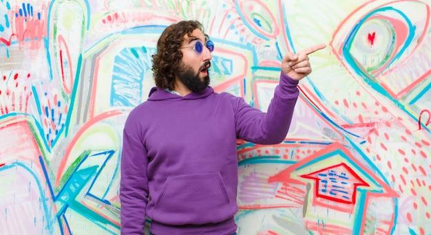 Junger bärtiger verrückter mann, der entsetzt und überrascht sich fühlt, in ehrfurcht mit erstauntem blick mit offenem mund gegen graffiti zeigt und nach oben schaut Premium Fotos