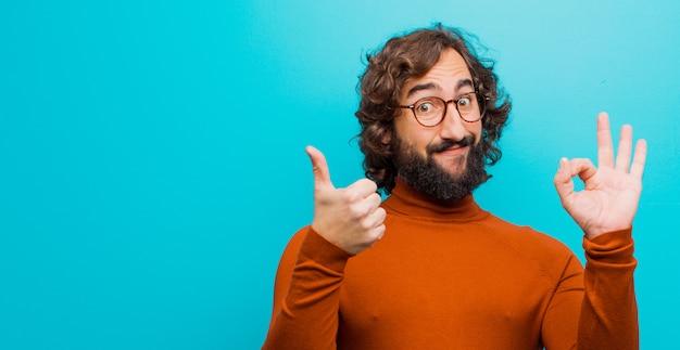 Junger bärtiger verrückter mann, der glücklich, überrascht, zufrieden und überrascht sich fühlt und ok und daumen herauf die gesten zeigt und gegen flache farbwand lächelt Premium Fotos