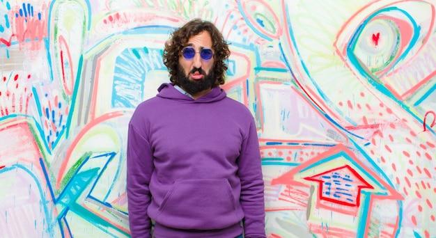 Junger bärtiger verrückter mann, der mit einem unglücklichen blick traurig und jammernd sich fühlt und mit einer negativen und frustrierten haltung gegen graffitiwand schreit Premium Fotos