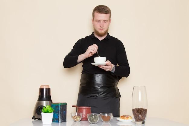Junger barista im schwarzen arbeitsanzug mit braunen kaffeesamen der zutaten und der kaffeeausrüstung auf weiß Kostenlose Fotos