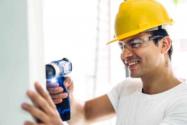 Junger bauarbeiter, der mit schraubenzieher arbeitet, um einen hauseingang einzubohren Premium Fotos