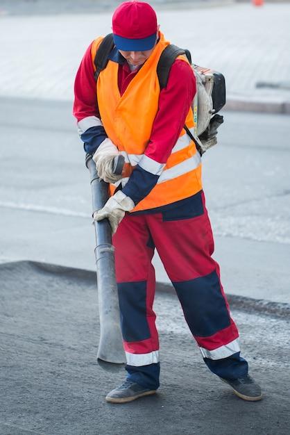 Junger baumeister auf asphaltierfertigermaschine während straßenstraßenreparaturarbeiten Premium Fotos