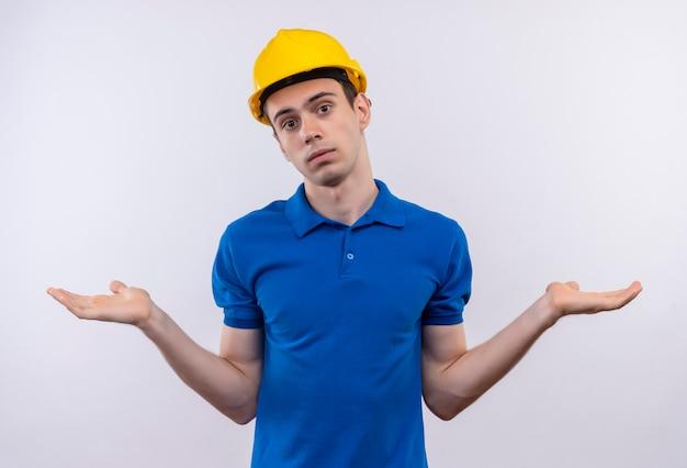 Junger baumeister, der bauuniform und schutzhelm trägt, weiß nicht, was zu tun ist Kostenlose Fotos