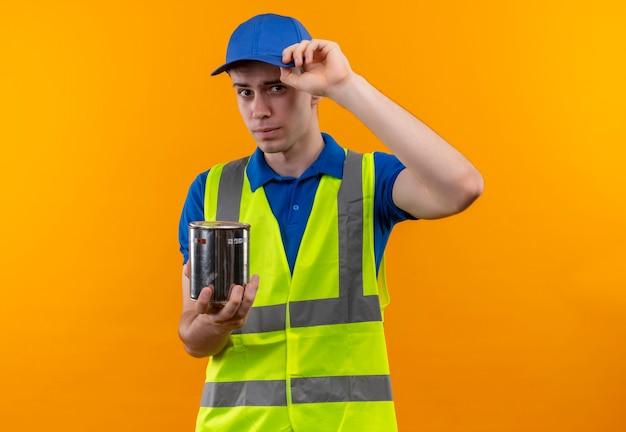 Junger baumeistermann, der bauuniform und kappe trägt, hält einen farbbehälter Kostenlose Fotos
