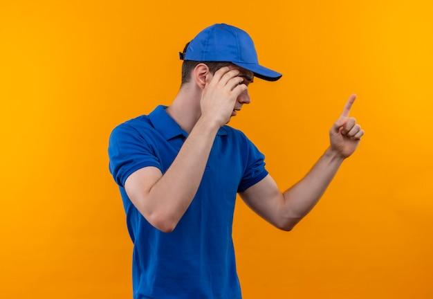 Junger baumeistermann, der bauuniform und mütze trägt, erklärt etwas mit einem finger Kostenlose Fotos