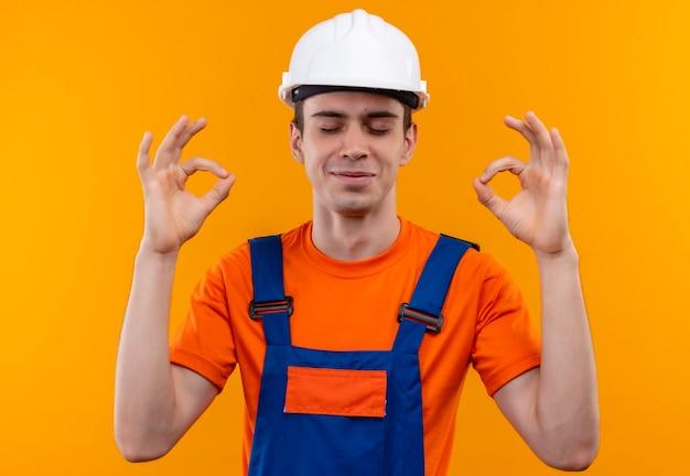 Junger baumeistermann, der bauuniform und schutzhelm trägt, der seine augen schließt und mit händen in ordnung tut Kostenlose Fotos