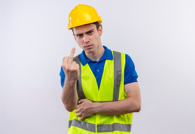 Junger baumeistermann, der bauuniform und schutzhelm trägt, zeigt ficken wütend Kostenlose Fotos