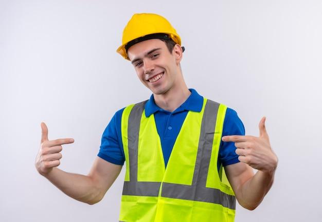 Junger baumeistermann, der bauuniform und sicherheitshelm trägt, der glücklich mit zeigefingern zeigt Kostenlose Fotos