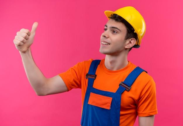 Junger baumeistermann, der bauuniform und sicherheitshelm trägt, die glückliche daumen hoch tun Kostenlose Fotos