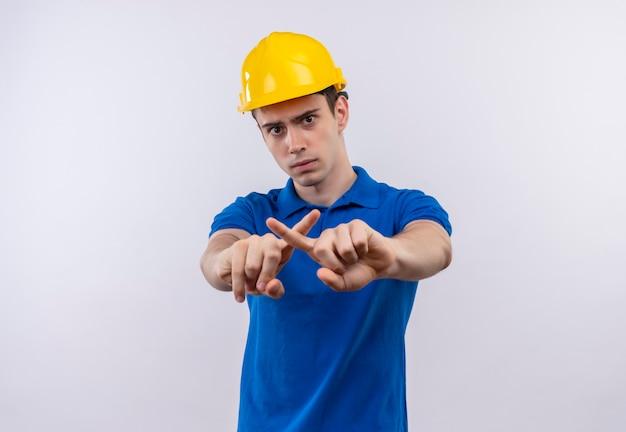 Junger baumeistermann, der bauuniform und sicherheitshelm trägt, kreuzt zeigefinger Kostenlose Fotos