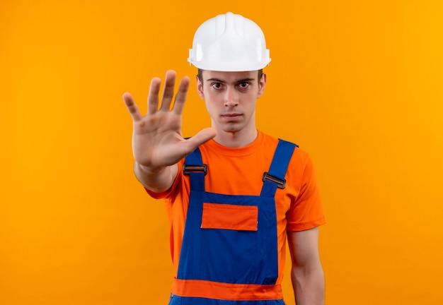 Junger baumeistermann, der bauuniform und sicherheitshelm trägt, stoppt mit der linken hand Kostenlose Fotos