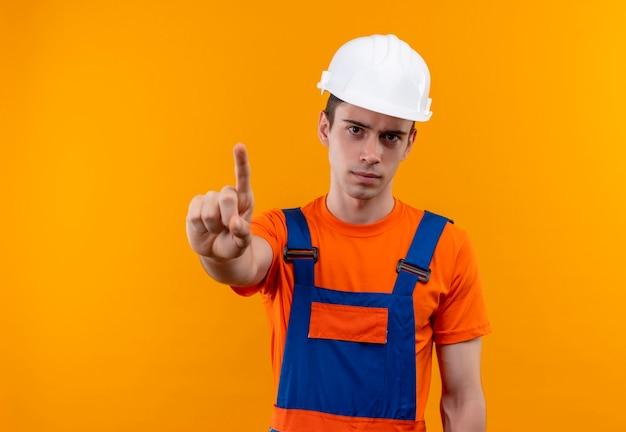 Junger baumeistermann, der konstruktionsuniform und sicherheitshelm trägt, der finger oben tut Kostenlose Fotos