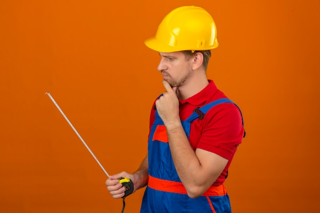Junger baumeistermann in bauuniform und sicherheitshelm, der auf maßband in seinen händen nachdenklichem blick über isolierte orange wand schaut Kostenlose Fotos