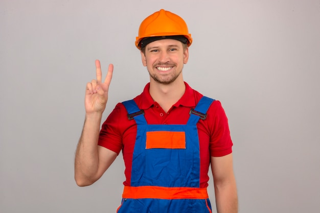 Junger baumeistermann in bauuniform und sicherheitshelm, der mit den fingern nummer zwei oder dem siegeszeichen zeigt und zeigt, während er zuversichtlich und glücklich über isolierte weiße wand lächelt Kostenlose Fotos